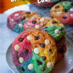 A plate of rainbow chocolate chip cookies with more rainbow chocolate chip cookies behind it.