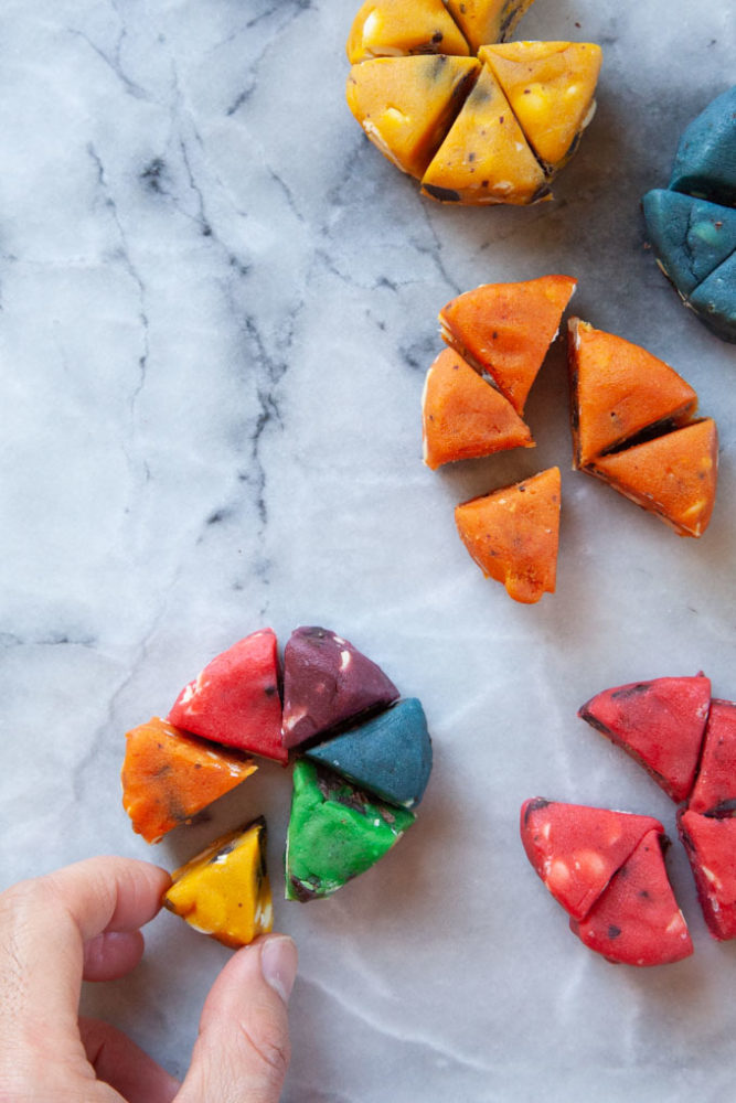 A hand assembling the colored pieces of cookie dough to make the rainbow cookie.