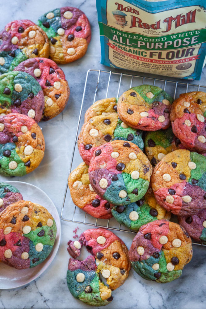 Rainbow chocolate chip cookies on a wire rack and on a plate, next to a bag of Bob's Red Mill all-purpose flour.