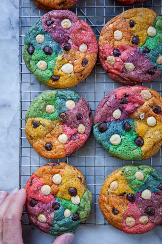 A hand reaching for a rainbow chocolate chip cookie cooling on a wire rack.